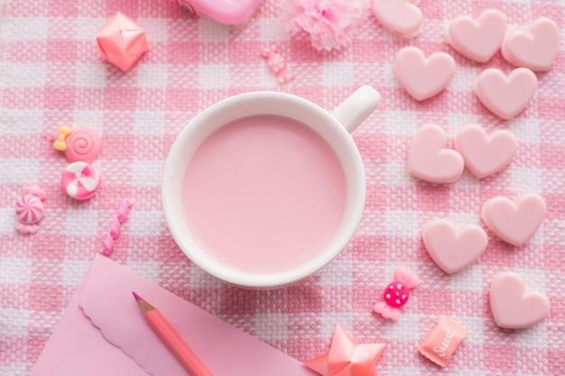 Fête de la saint-valentin avec une tasse de lait sur une nappe rose