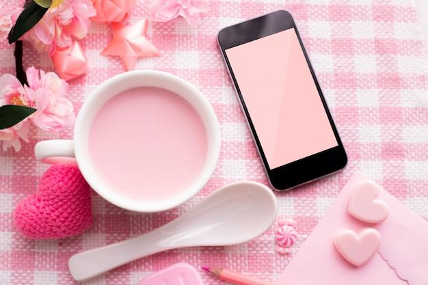 Fête de la saint-valentin avec tasse de lait et smartphone écran blanc.