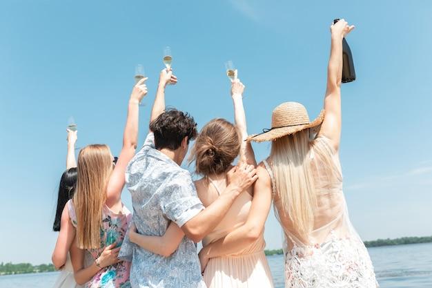 Fête saisonnière au groupe d'amis de la station balnéaire célébrant le repos en s'amusant sur la plage