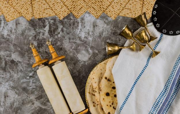 Fête traditionnelle du jour de la pâque avec quatre tasse de vin et du pain sans levain matsa casher sur rouleau de la torah de la fête juive de pessa'h