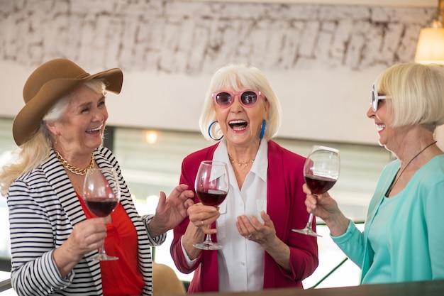 Fête. trois dames heureuses senior faisant la fête et semblant appréciées en buvant du vin