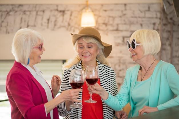Fête. trois dames heureuses seniors faisant la fête et semblant appréciées en buvant du vin