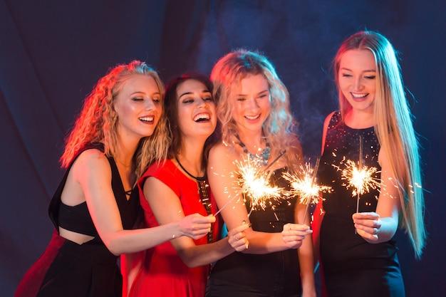 Fête de vacances nouvel an noël et concept de vie nocturne heureux jeunes femmes dansant au night club