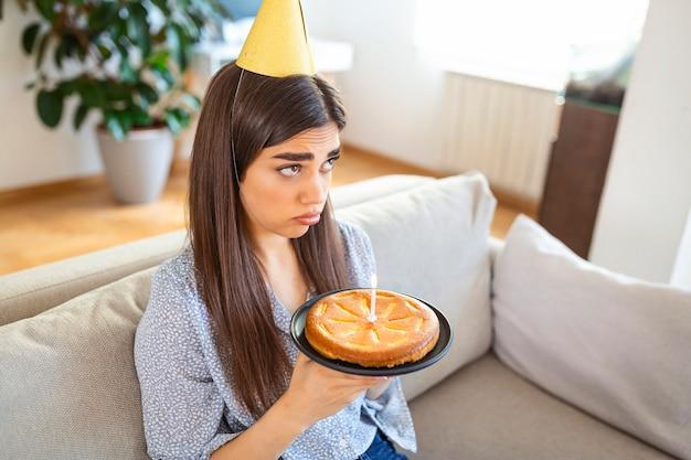 Fête virtuelle pendant le verrouillage. femme afro-américaine célibataire bouleversée et frustrée en chapeau de fête célébrant son anniversaire en ligne. dame faisant une vidéoconférence, tenant un gâteau avec une bougie, assise sur le sol