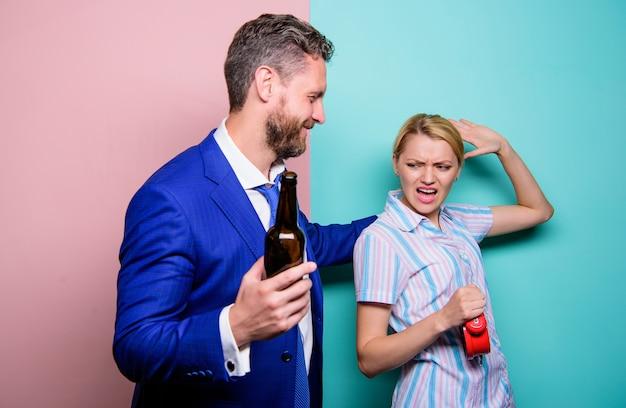 Fêtons. femme montre l'heure sur l'horloge. femme se demandant pourquoi mari fêtard est rentré si tard. routine familiale. problèmes dans la relation. psychologie familiale. vie malheureuse. homme boisson alcoolisée du vin.
