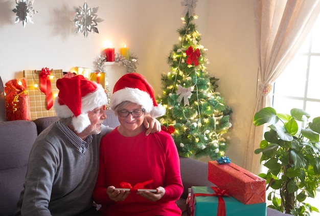 Fêtons noël ensemble. un beau couple de personnes âgées profitant de l'échange de cadeaux. ils portent des chapeaux de père noël. bel arbre de noël en arrière-plan et cadeaux pour la famille