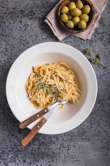 Fettucini alfredo dans une assiette aux olives