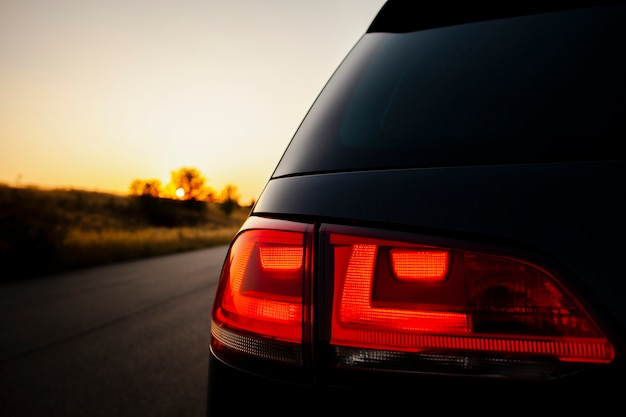Feu arrière rouge sur le fond du beau coucher de soleil