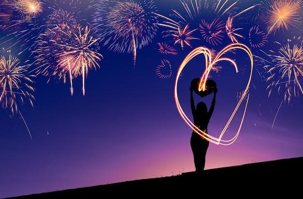 Feu d'artifice coeur avec la silhouette de la femme sur fond de ciel violet crépuscule