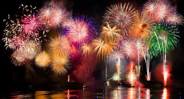 Feu d'artifice coloré. les feux d'artifice sont une classe de dispositifs pyrotechniques explosifs utilisés à des fins esthétiques et de divertissement. bruit visible dû à une faible luminosité, mise au point douce, dof peu profond, léger flou de mouvement
