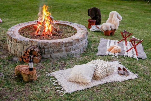 Feu de bois avec bancs dans le jardin au coucher du soleil