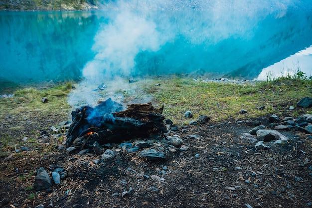 Feu de camp atmosphérique sur la rive du lac de montagne