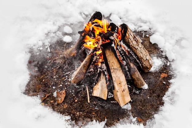 Un feu de camp brûle dans la neige dans les bois