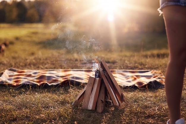 Feu de camp sur l'herbe verte, le plaid se trouve à proximité, belle nature, atmosphère calme, soleil, aucun peuple sur la photo. vacances d'été