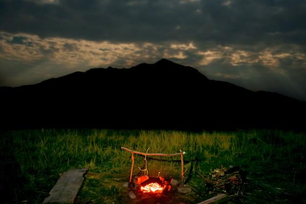 Feu de camp sur pelouse verte près de la montagne la nuit avec ciel sombre et clair de lune