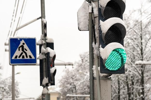 Un feu de circulation dans une rue de la ville en hiver. le feu de circulation est vert