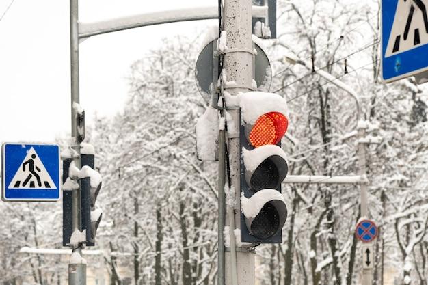 Un feu de circulation dans une rue de la ville en hiver. le feu rouge du feu est allumé