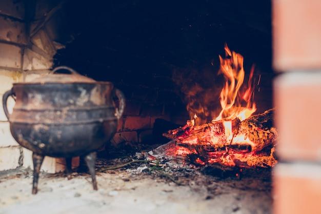 Feu confortable dans une cheminée en pierre avec pichet