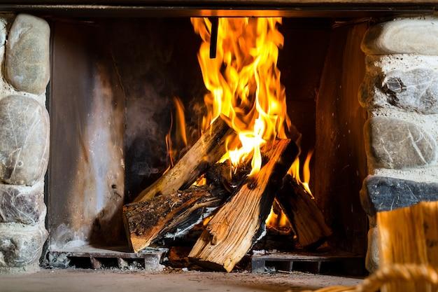 Feu dans une cheminée rustique dans une cabane de montagne traditionnelle