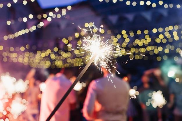 Feu du bengale sur le fond de la fête, des gens dansants et des lumières colorées