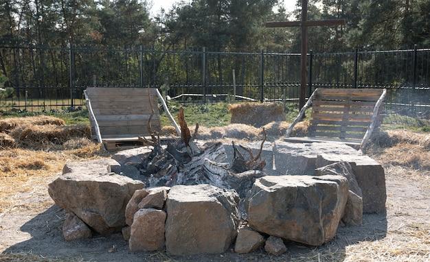 Un feu fait maison clôturé avec des pierres et deux bancs à proximité