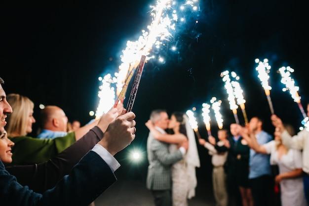 Feu froid des bougies de gâteau et des feux d'artifice dans les mains des personnes autour des jeunes mariés