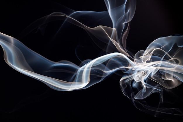 Feu de fumée abstraite bleue et blanche sur fond noir, concept d'obscurité