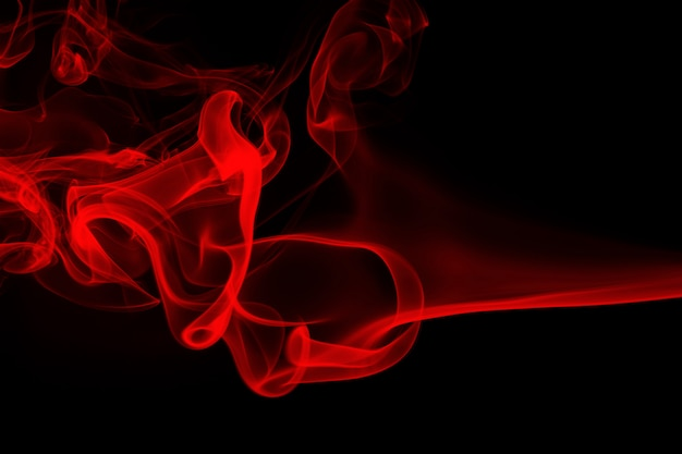 Feu de fumée rouge abstrait sur fond noir, concept d'obscurité