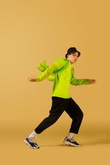 Feu. jeune homme façonné à l'ancienne dansant isolé sur fond de studio jaune. mode d'artiste, concept de mouvement et d'action, culture des jeunes, retour de la mode. jeune garçon bouclé caucasien.