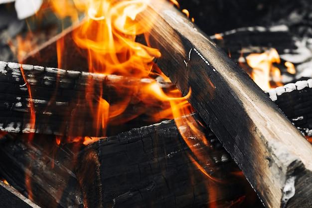 Feu de joie dans la forêt. gros plan du feu de camp flamboyant, feu de camp brûlant des bûches dans de grandes flammes orange et jaunes en gros plan sur le bois en feu. cheminée brûlante avec flammes et braises incandescentes.