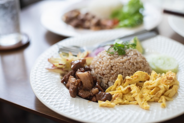 Feu de riz avec du porc et œuf de feu sur une table en bois