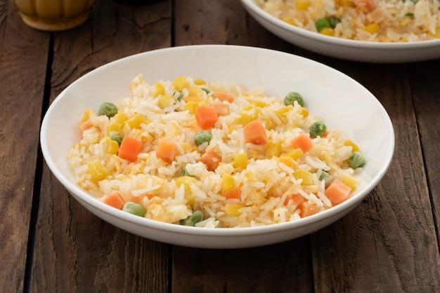 Feu de riz avec des légumes sur une plaque blanche