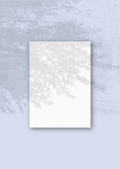 Une feuille a4 verticale de papier texturé blanc sur le mur bleu
