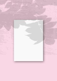 Une feuille a4 verticale de papier texturé blanc sur le mur rose