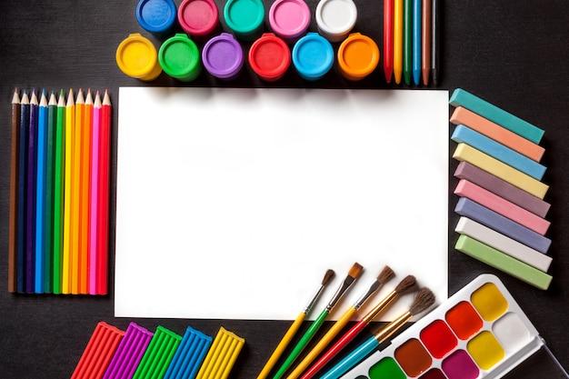 Feuille d'album blanche et propre. outils pour la peinture et l'art sur fond noir.
