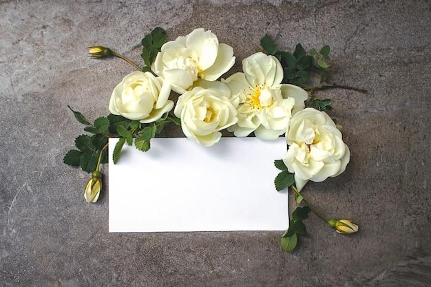 Feuille d'autocollants vierges à plat pour les maquettes de produits et les publications sur les réseaux sociaux. doté d'une carte vide entourée de fleurs.