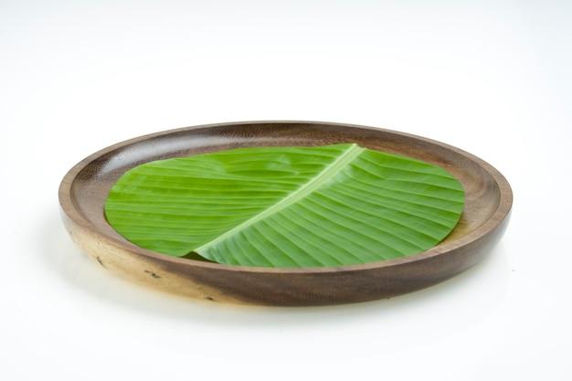 Feuille de bananier feuille de bananier verte fraîche coupée en forme circulaire et placée sur une plaque en bois