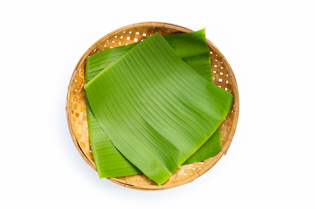 Feuille de bananier sur panier en bambou sur blanc