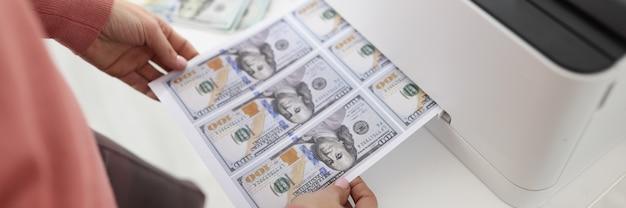 La feuille avec des billets de banque américains sort de l'économie de l'imprimante et du concept de presse à imprimer