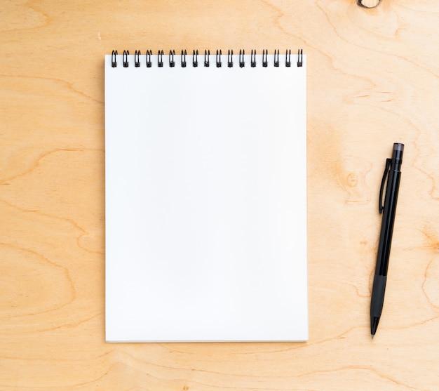 Feuille blanche de cahier une spirale sur un fond en bois beige neutre, vue de dessus.