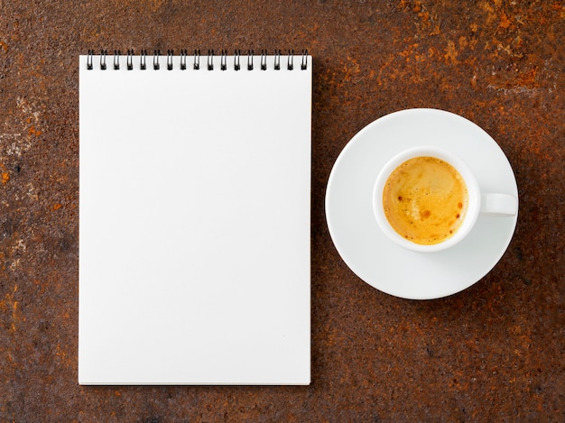 Feuille blanche de cahier une spirale et une tasse de café sur la vieille table de fer rouillée, vue de dessus.