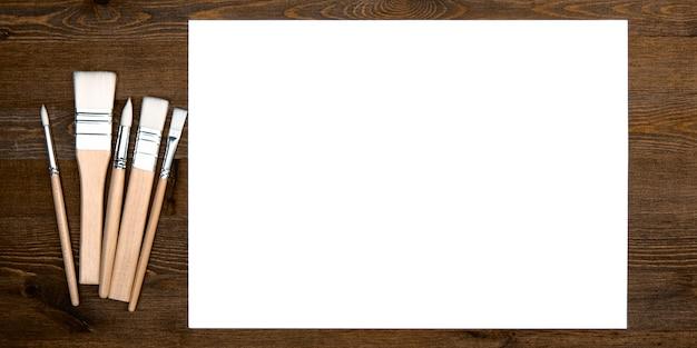 Une feuille blanche propre et des pinceaux sur un fond texturé en bois avec un espace pour copier.