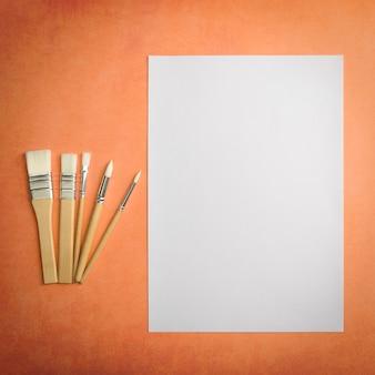 Une feuille blanche propre et des pinceaux sur un fond texturé avec un espace pour copier l'espace de maquette de mise en page