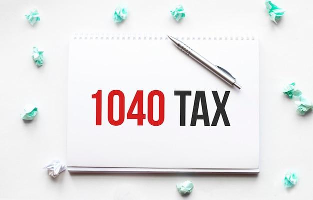 Feuille blanche, stylo et boules de papier froissé sur table grise, pose à plat. texte 1040 taxe