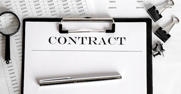 Feuille blanche avec le texte du contrat à la surface des documents et des graphiques