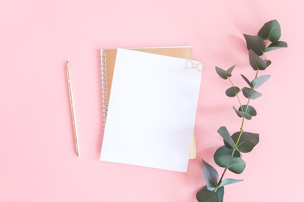 Feuille blanche vierge sur bloc-notes en spirale dorée avec trombone coeur, crayon et branche verte d'eucalyptus sur fond pastel rose.