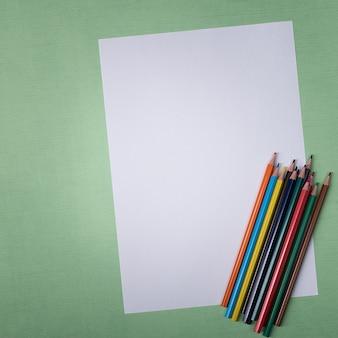 Une feuille blanche vierge et des crayons de couleur pour dessiner sur un fond texturé uni avec espace