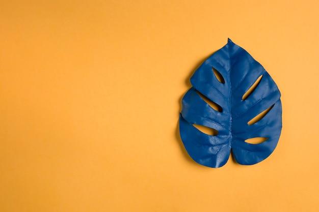 Feuille bleue sur fond orange avec espace de copie