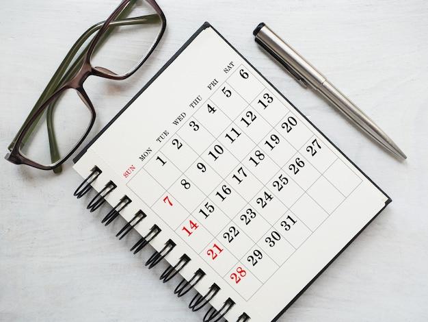 Feuille de bloc-notes et calendrier vierges pour votre message de félicitations. gros plan, vue de dessus. personne. concept de préparation pour des vacances. félicitations aux parents, amis et collègues