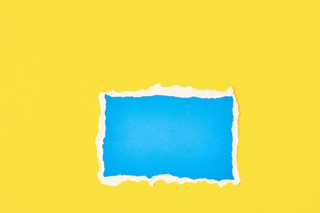 Feuille de bord déchiré en papier bleu déchiré sur fond jaune